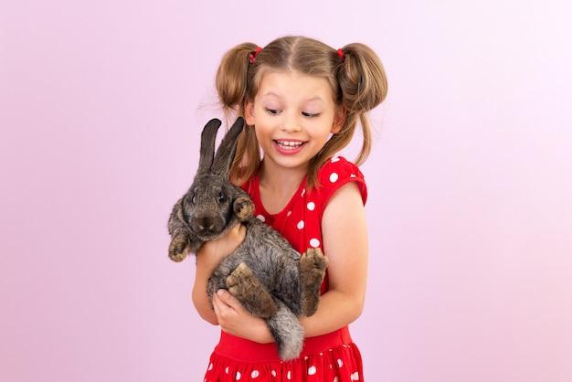 Ребенок держит в руках маленького кролика. девушка с кроликом на изолированном фоне.