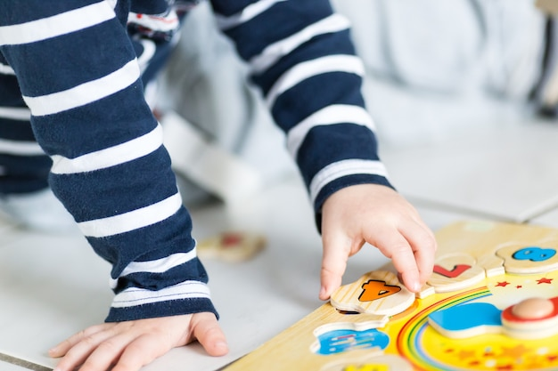 子供は木製の時計パズルで遊んでいます