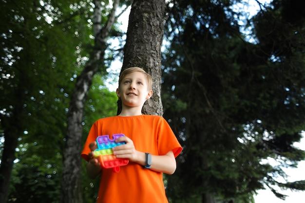 Ребенок стоит в парке, прислонившись спиной к дереву, держа в руках антистрессовую силиконовую игрушку.
