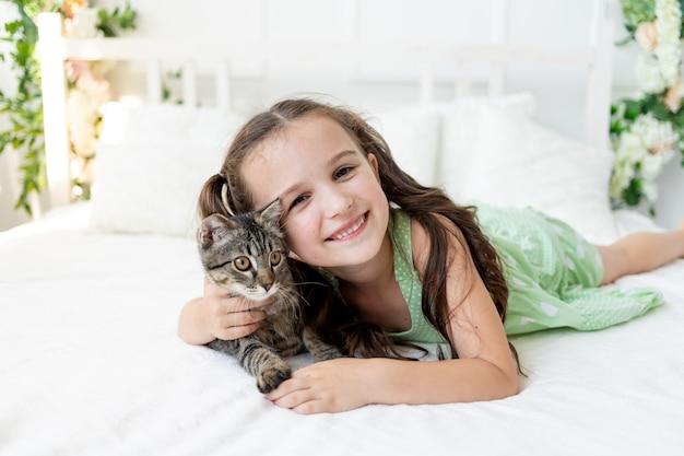 Ребенок мучает животное, маленькая девочка с кошкой лежит на кровати, концепция дружбы ребенка с животными