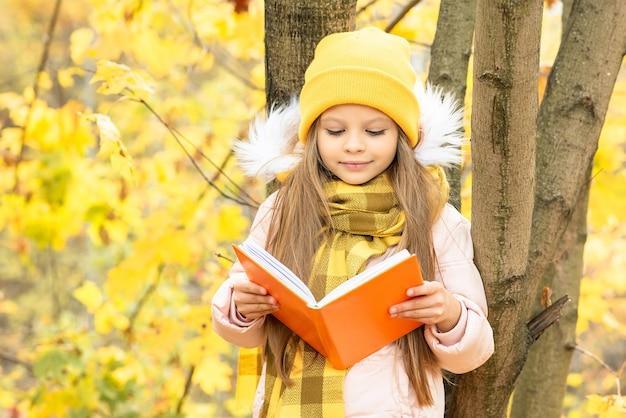 子供が木にもたれて秋の本を読みます。