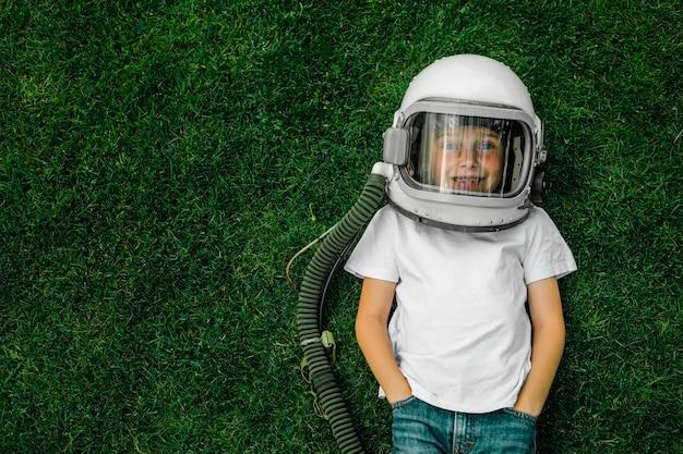 Ребенок в шлеме космонавта лежит на траве и мечтает о великих свершениях!