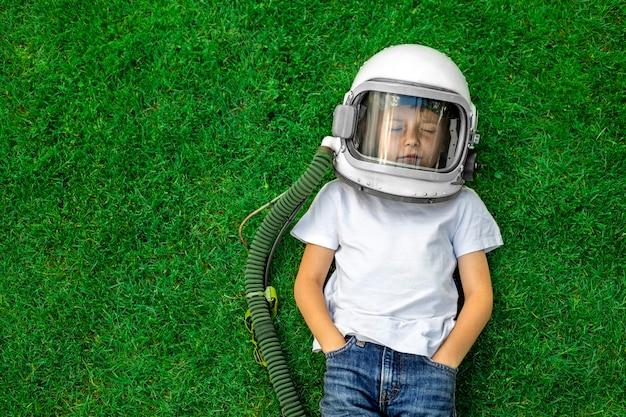 子供が宇宙飛行士のヘルメットをかぶって草の上に横たわり、素晴らしい成果を夢見ています!