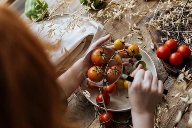 Ребенок смотрит в лупу на маленькие помидоры на ветке.