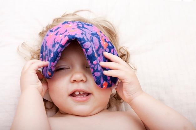 Ребенок, лежащий на подушке, надевает маску для сна на глаза