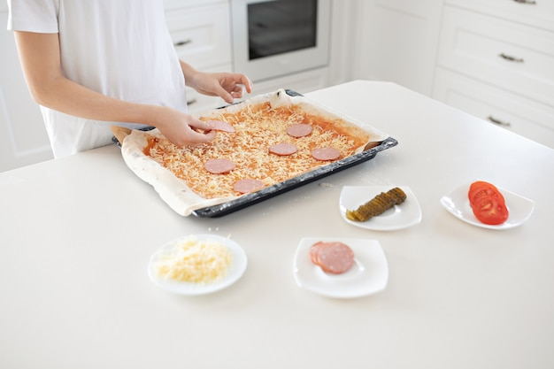 子供がピザを作ります。サラミ、チーズ、ケチャップ、トマト、きゅうり。
