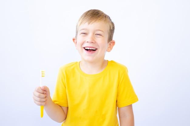 Ребенок на белом фоне чистит зубы, держа в руках зубную щетку изолировать