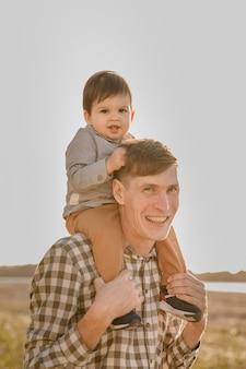彼の父親の首に子供。水の近くを歩きます。空に対して赤ちゃんとお父さん。