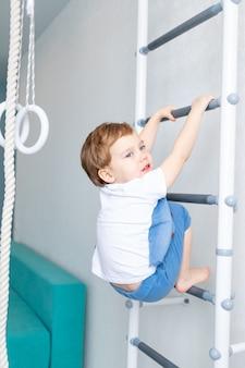 스웨덴 벽에있는 아이가 집에서 스포츠를하고, 소년은 스포츠와 건강의 개념 인 밧줄로 사다리를 올라갑니다.
