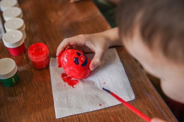 아이가 부활절 달걀에 빨간 구 아슈를 칠하고 그 위에 얼굴을 그립니다.