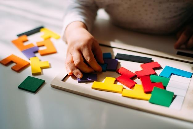 Ребенок играет на столе в цветной пазл.