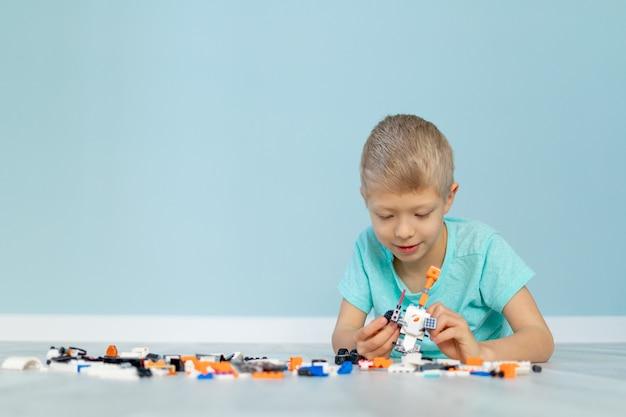 한 아이가 파란색 배경에 집 건설자와 함께 놀고 있다