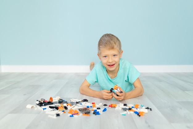 아이가 파란색 배경에 레고 하우스 생성자로 재생