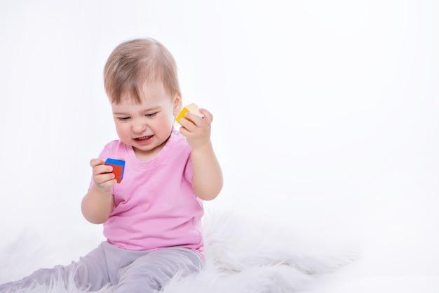 子供はカラフルな数字で遊ぶ。手の中のおもちゃの詳細。サイコロを保持している女の子