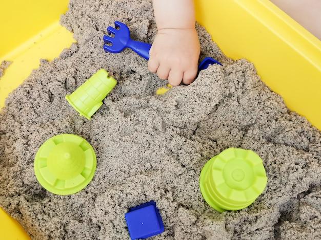 아이가 운동 모래를 가지고 노는 : 아이의 손과 모래의 근접 촬영.