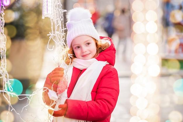 街のお祝いに飾られたクリスマスマーケットで、赤毛の子供が歩いて花輪のある屋台を眺めます。