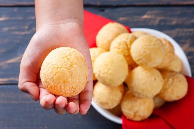 브라질 치즈 빵을 들고 아이의 손. 라틴 아메리카에서는 chipa, pan de bono 및 pan de yuca로도 알려져 있습니다.