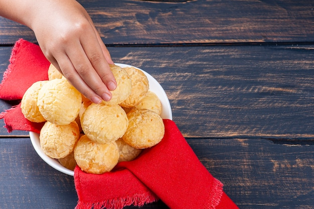브라질 치즈 빵을 집는 아이의 손. 라틴 아메리카에서는 chipa, pan de bono 및 pan de yuca로도 알려져 있습니다.