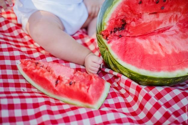 Детская нога и разрезанный арбуз. ножка ребенка на пледе и кусочек арбуза.