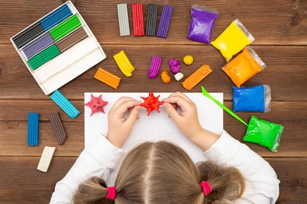 한 아이가 코로나 바이러스 코로 노 바이러스 모델을 집에서 플라 스티 신으로 조각합니다.