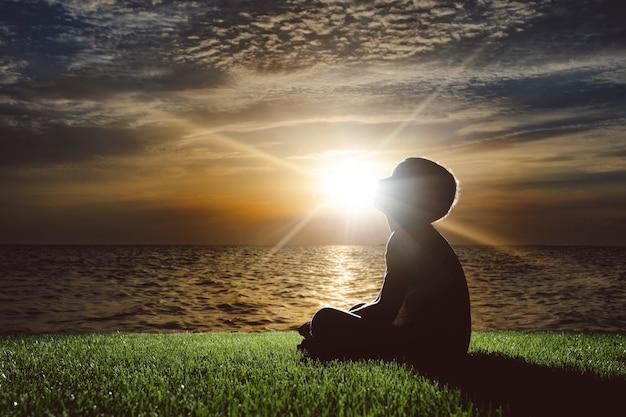 아이는 일몰과 꿈에 바다에 앉아