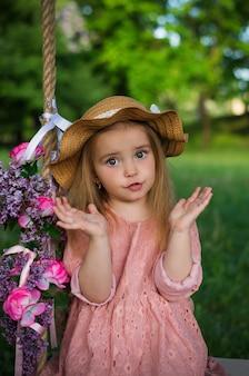 子供が公園のブランコに座っている女の子の驚きの顔