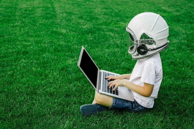 Ребенок сидит на траве в шлеме космонавта и занимается на ноутбуке онлайн, наслаждаясь природой.