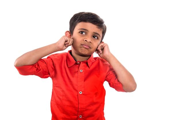 Ребенок улыбается и дергает за уши на белой стене