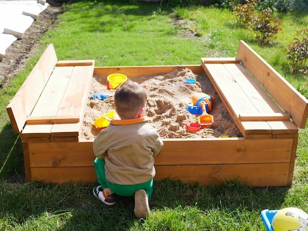 Ребенок проводит время, играя в песочнице