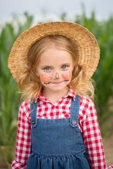 子供がトウモロコシ畑、かかし、ハロウィーンに立っています