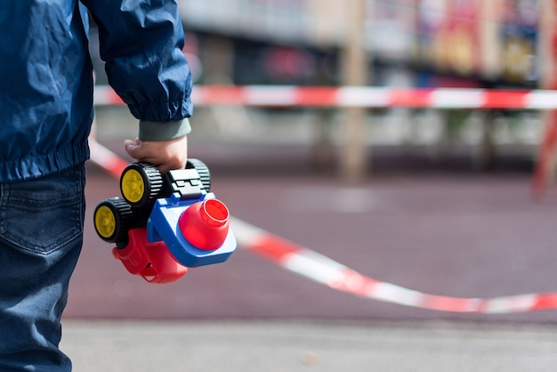 赤いリボンで囲われた遊び場の上に立っている子供がおもちゃの車を手に持っている