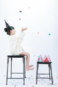 검은 파티 모자를 쓰고있는 아이가 의자에 앉아 그의 어머니가 던지는 색종이 가루를 보면서 재미있게 놀아요.