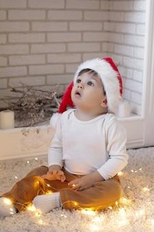 Ребенок в шляпе санта-клауса сидит у белого камина с огнями рождественской гирлянды и смотрит вверх.