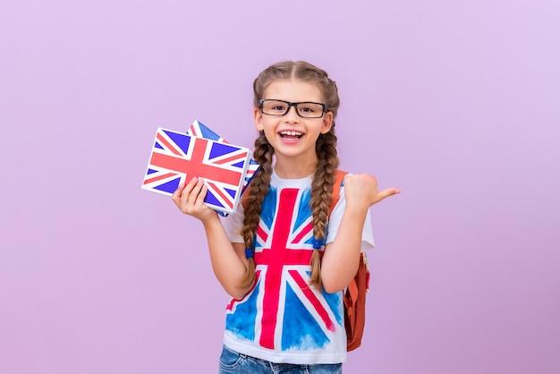 안경을 쓰고 영국 국기가 달린 티셔츠를 입은 아이가 분홍색 외진 배경에 손에 영어 책을 들고 있습니다.