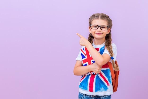 Ребенок в очках и футболке с британским флагом держит в руке английские книги на розовом изолированном фоне.