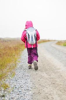 배낭을 메고 흙길을 걷는 아이