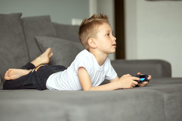 Ребенок с джойстиком в руках лежит дома на диване и играет на консоли