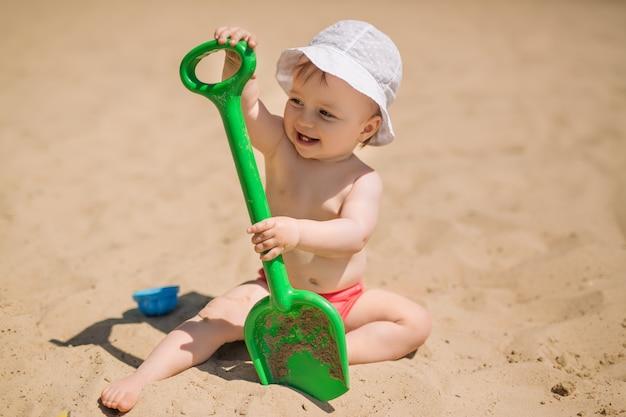 더운 날에 모래 해변에 큰 녹색 장난감 삽을 가진 아이