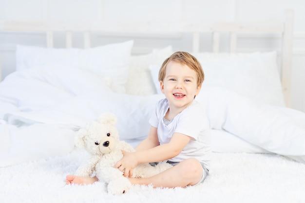 집에서 침대에 테디 베어를 안고있는 아이가 놀고 웃는다