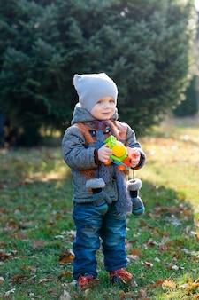 Ребенок с игрушкой в руках на прогулке в парке