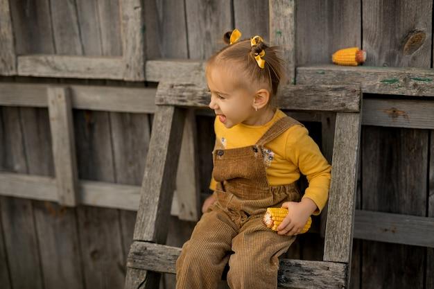とうもろこしの穂を手にした子供が木製の脚立に座って目をそらします