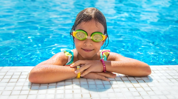 眼鏡をかけた子供がプールに飛び込みます。セレクティブフォーカス。