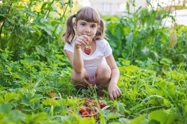 Ребенок с клубникой в руках