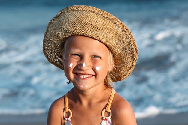 日焼け止めを顔につけた子供がカメラを見て微笑む