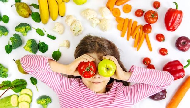 手に野菜や果物を持っている子供