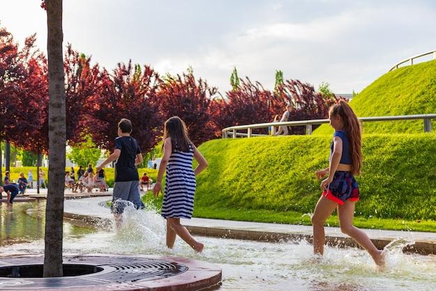 공원 분수대에서 물놀이를 하는 아이들. 더운 여름.