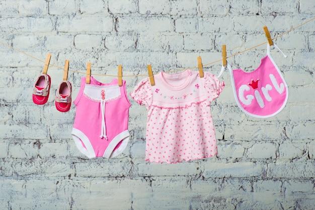 子供のピンクのボディよだれかけドレスと白いレンガの壁にロープで乾いた女の子のための赤い靴