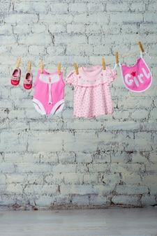 흰색 벽돌 벽에 밧줄에 마른 소녀를위한 어린이 분홍색 몸통 턱받이 드레스와 빨간 신발