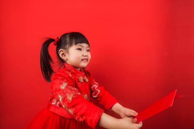 중국 소녀는 빨간 봉투로 구정을 축하합니다