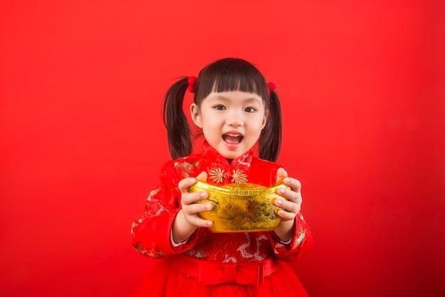 中国の女の子が金の延べ棒で春節を祝います。金の延べ棒の中国語訳:金の延べ棒の富